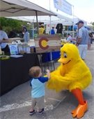 Life-sized yellow duck giving a small child a high-five