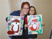 Mother and daughter holding up paintings of a fox