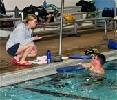 Swim instructor on pool deck with adult studen in water at pool edge