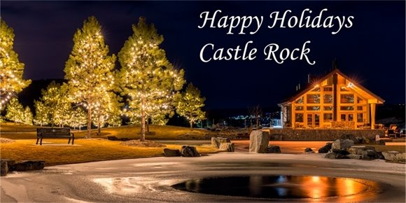 Winter photo of the Millhouse and pond lite up with the words Happy Holiday Castle Rock