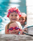 2 gills with goggles and swim cap at edge of pool