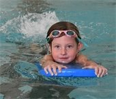 girl with goggles on head using a kickboard in the pool