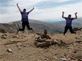 Two ladies jumping for joy at the top of a 14er