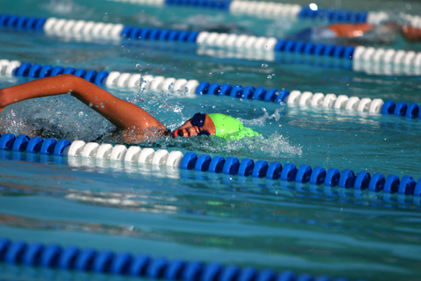A swimming in the lanes with a bright green swim cap