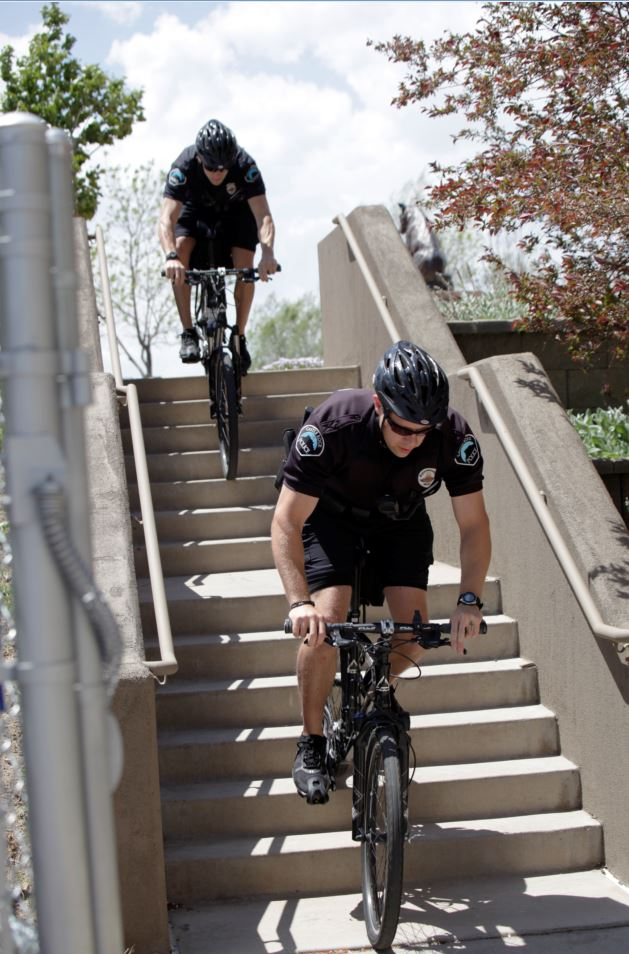 Police bike unit riding bike down stairs