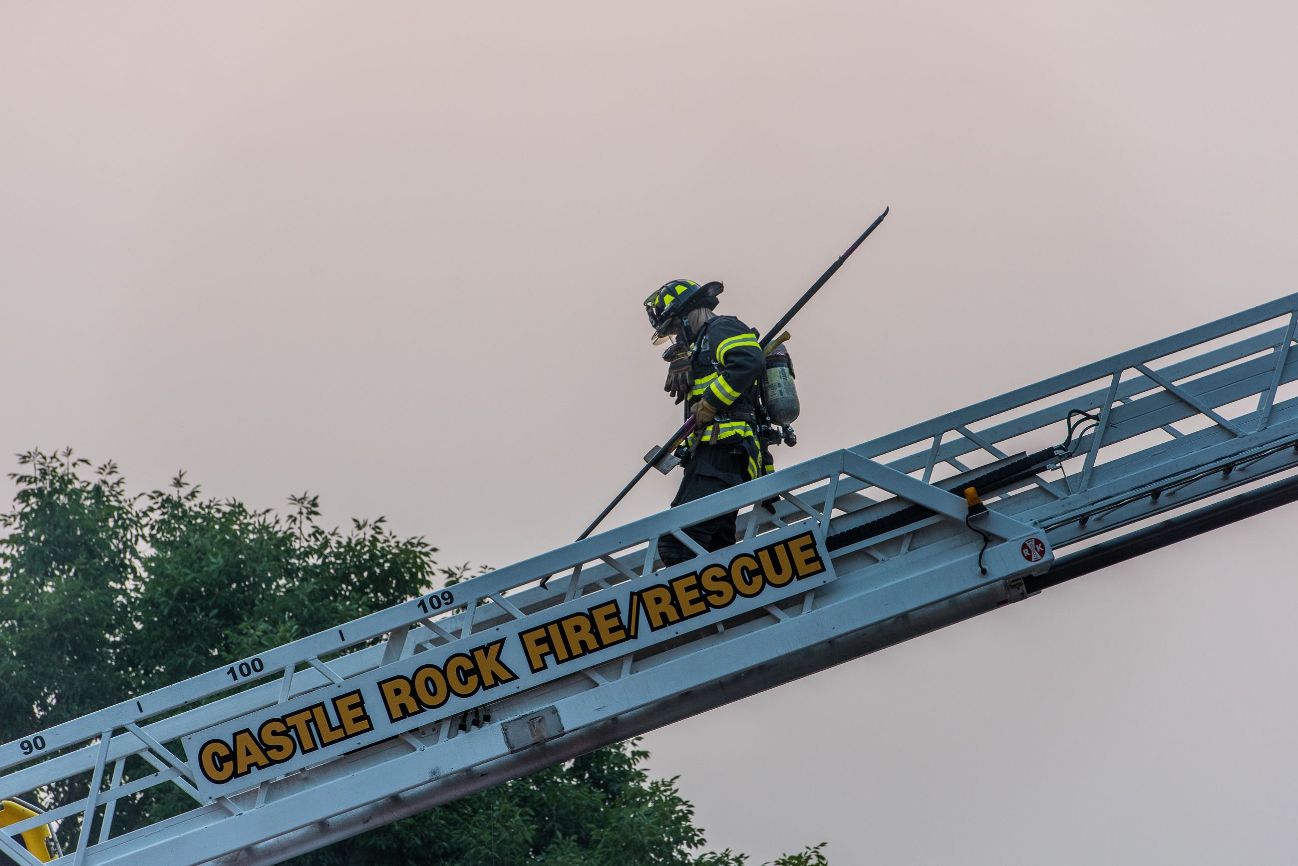 Firefighter walks down the fire truck's ladder
