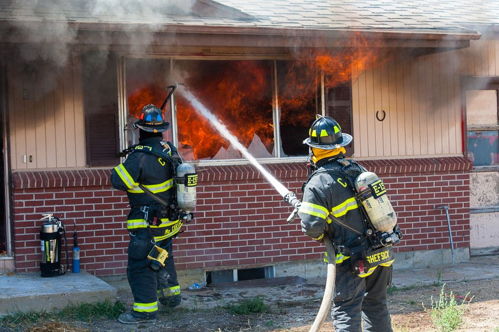 Firefighters fighting a house fire with hose and water