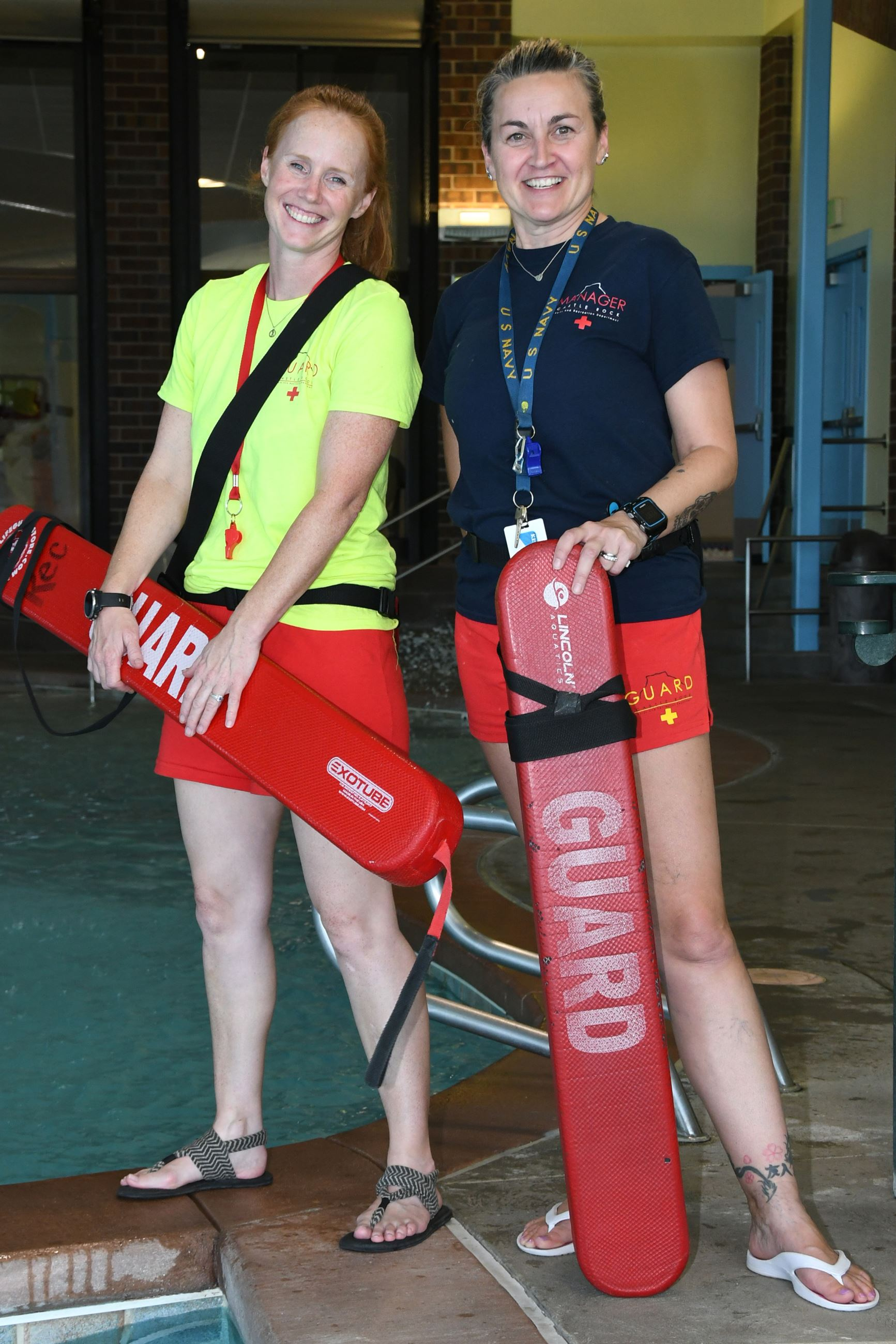 Adult female lifeguards standing poolside