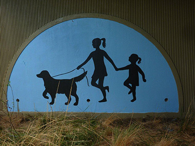 A mural of the silhouette of 2 girls holding hands and walking a dog